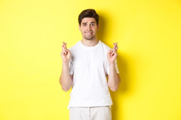 Ragazzo nervoso che incrocia le dita per buona fortuna, sperando in qualcosa, in piedi su sfondo giallo.