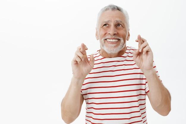 Uomo anziano nervoso speranzoso incrocia le dita, buona fortuna e pregando, esprimendo un desiderio