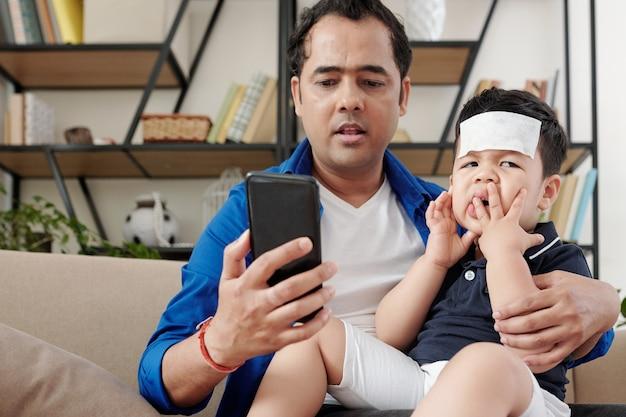 소아과 의사에게 전화를 걸고 아픈 장난 꾸러기 아들과 긴장된 인도 남자