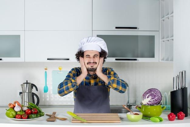 Chef maschio nervoso con verdure fresche e cucinare con utensili da cucina e chiudere le orecchie nella cucina bianca