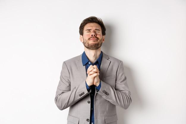 Нервный мужчина-предприниматель в костюме умоляет бога, взявшись за руки в молитве с умоляющим выражением лица, закрывает глаза и загадывает желание, прося о помощи, стоя на белом фоне.