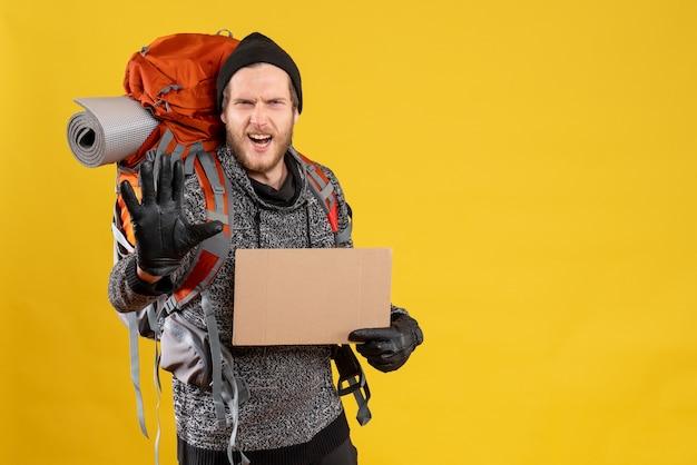 Нервный мужчина-автостопщик с кожаными перчатками и рюкзаком держит пустой картон, делая знак остановки