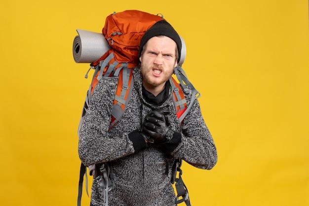革手袋とパンチを示すバックパックを持つ神経質な男性ヒッチハイカー
