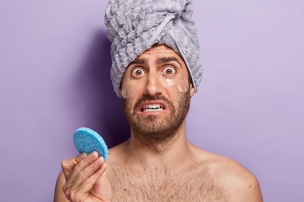 Aspetto maschile nervoso con espressione del viso preoccupata e dispiaciuta, trattiene la spugna cosmetica, applica cerotti idrogel per rimuovere le borse sotto gli occhi