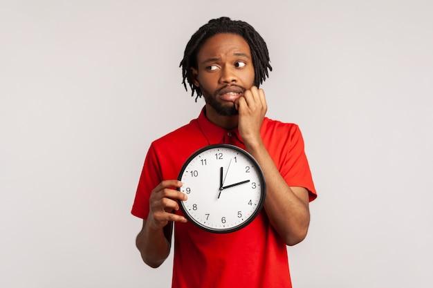 Нервный мужчина кусает ногти на пальцах, держа в руке большие настенные часы, беспокоясь о сроках.