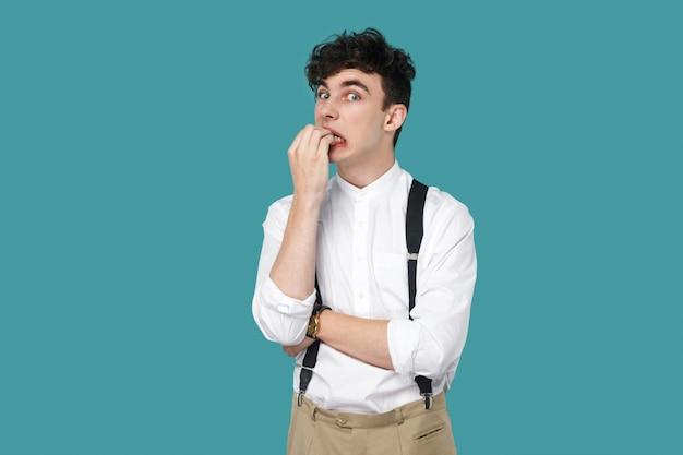 爪を噛んでカメラを見ている神経質な男。クラシックなカジュアルな白いシャツ、サスペンダー立っているハンサムな流行に敏感な巻き毛の青年実業家の肖像画。青い背景に分離された屋内スタジオショット。