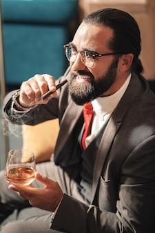 Нервный мужчина. усталый нервный бородатый темноволосый мужчина курит сигару и смотрит в окно