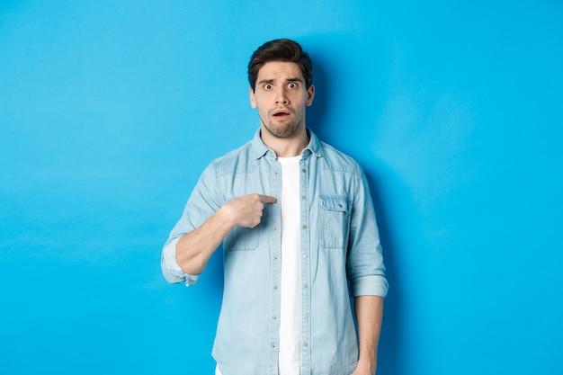 青い背景の上にカジュアルな服を着て立って、自分自身を指して混乱しているように見える神経質な男。