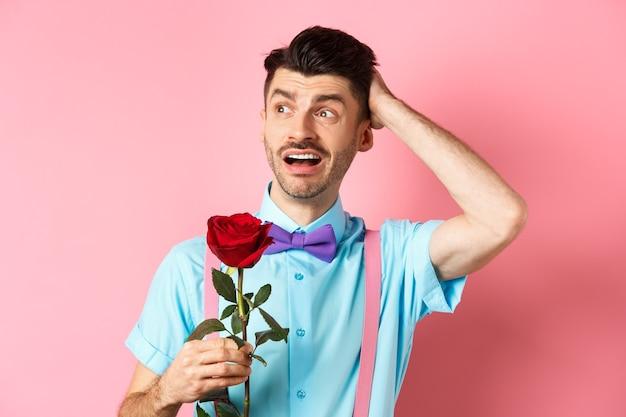 Нервный мужчина ждет своего свидания в день святого валентина, держит красную розу и смущенно смотрит в сторону