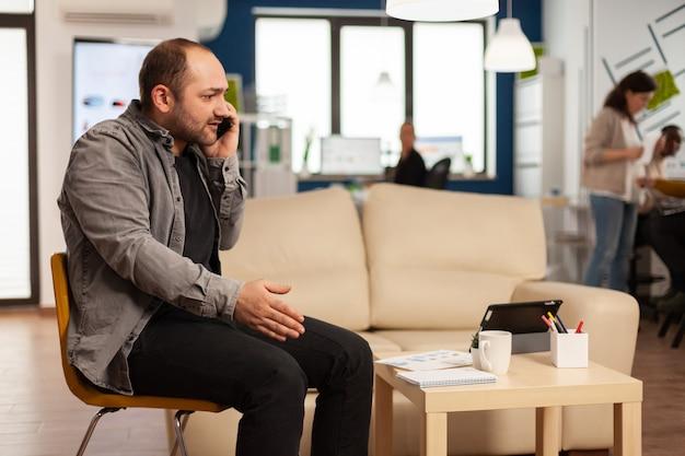 神経質なマネージャーが電話と呪いで積極的に話し、営業所の真ん中で椅子に座って叫ぶ