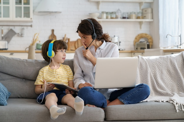 Nervous mother sitting on couch at home during lockdown work on laptop child distracts from work