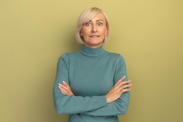 La donna slava abbastanza bionda nervosa sta con le braccia incrociate su verde oliva