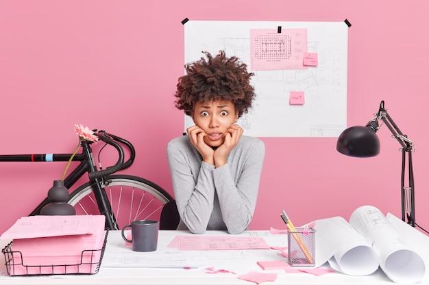 긴장된 의아해 아프리카 계 미국인 여성이 캐주얼하게 옷을 입고 시작 프로젝트 작업에 직장에 앉아 스케치를 그립니다