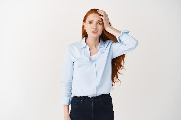 신경질적인 빨간 머리 여성은 걱정스럽고 화가 나서 머리를 만지고 죄가 있는 정면을 바라보며 무언가를 잊어버리고 흰 벽 위에 서 있다