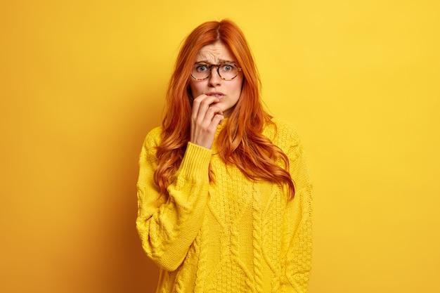 불안한 빨간 머리 젊은 여자는 당황한 찡그린 얼굴이 광학 안경과 스웨터를 착용하는 것을 걱정하는 것 같습니다.