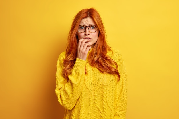 Nervous redhead young woman looks worried feels embarrassed frowns face wears optical glasses and sweater.