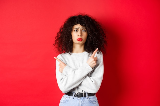 Nervous sad girl with curly hair, sobbing miserable and pointing fingers sideways, showing two things and look indecisive, red background