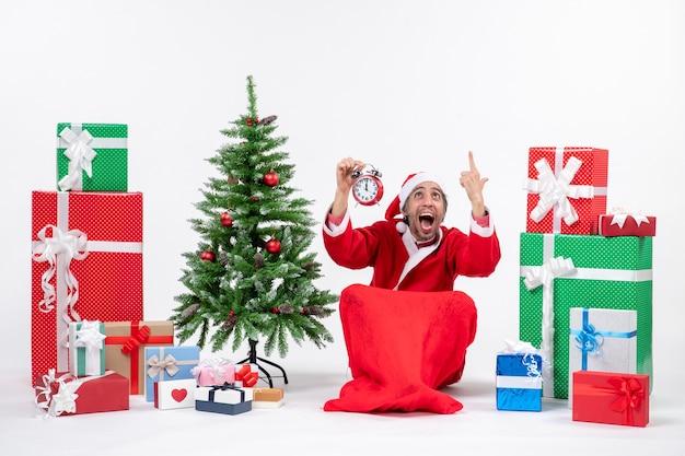地面に座って、贈り物の近くで時計を上げて、白い背景にクリスマスツリーを飾った神経質なサンタクロース