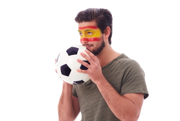 Tifoso nervoso con pallone da calcio che guarda avanti