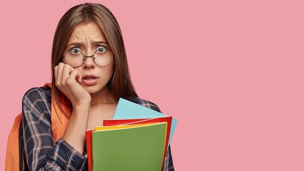 Studente stressante nervoso in posa contro il muro rosa con gli occhiali