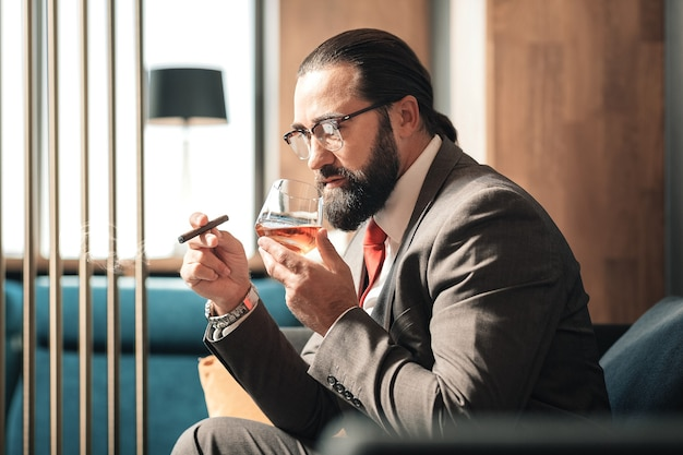 Nervous and tired. bearded mature ceo drinking and smoking feeling nervous and tired after negotiation