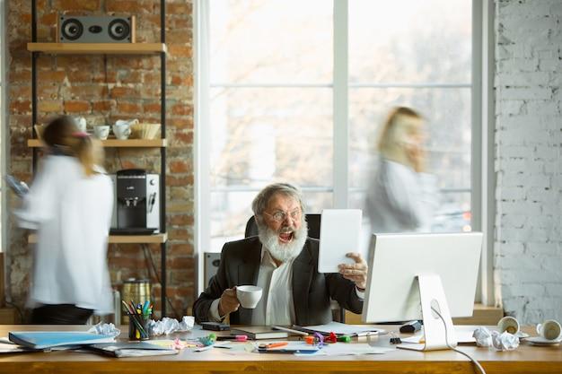 Capo nervoso e stanco al suo posto di lavoro occupato mentre le persone si muovono vicino sfocate. impiegato, manager che lavora, ha problemi e scadenze, i suoi colleghi distraggono. affari, lavoro, concetto di carico di lavoro.