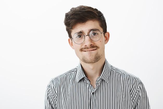 Нервный неуверенный смешной бородатый парень в круглых очках, кусающий губу и слегка хмурящийся, чувствующий себя неуверенно и неуверенно, желая спросить босса о повышении оплаты через серую стену