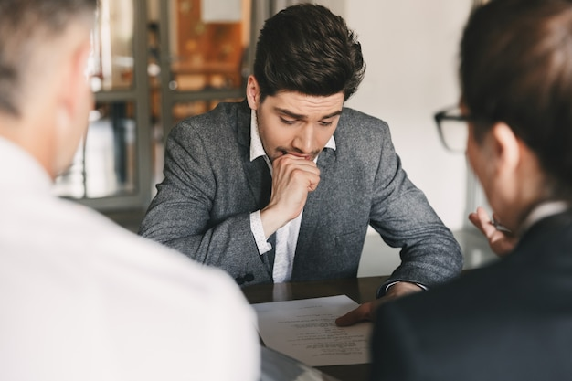 Nervous uptight man 30s worrying and biting fist during job interview in office, with collective of specialists - business, career and recruitment concept