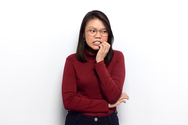 若い美しいアジアの女性の口に手で神経質な白で隔離の赤いシャツを着る
