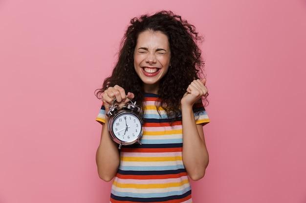 ピンクで隔離の目覚まし時計を保持している巻き毛の神経質な女性20代
