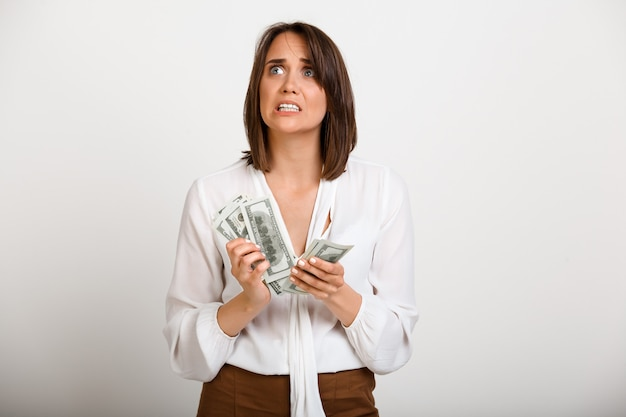 Nervous woman count money need pay debt