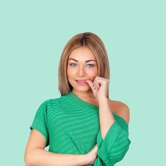 Нервная женщина, есть ее ногти, изолированных на зеленом фоне
