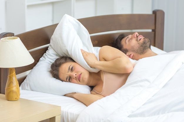 The nervous woman ley near the snore man in the bed