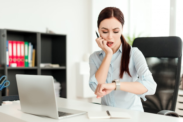 Nervous woman looking at her watch checking time in the office