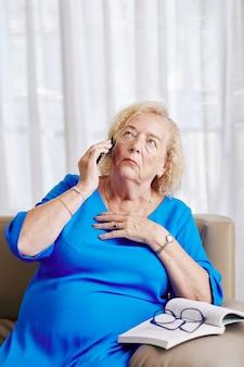 電話で話している神経質な女性
