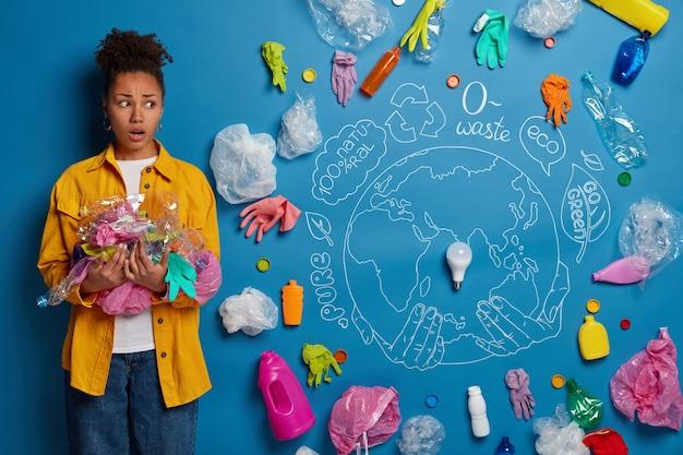 Donna afroamericana nervosa e preoccupata in camicia gialla protegge l'ambiente dalla spazzatura, raccoglie i rifiuti, preoccupata dall'inquinamento da plastica, responsabile della pulizia del territorio.
