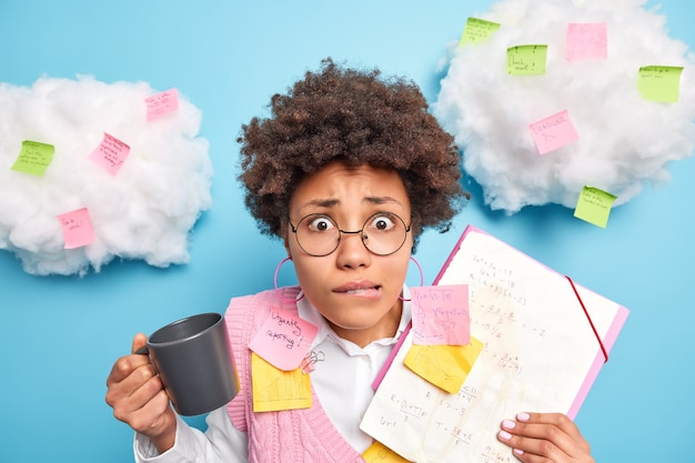 수학에서 기말 고사를 통과하는 것을 두려워하는 불안한 여학생이 입술을 물고 음료수 커피 주위에 수식과 다채로운 스티커가있는 종이를 들고 시험 세션을 준비합니다.
