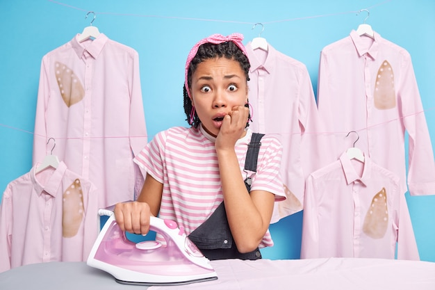 험상을 앓고있는 불안한 하녀가 집에서 다림질을하면 집에 대한 일이 많다. 당황한 짙은 피부의 여성 세탁소가 세탁소 나 세탁소에서 일함