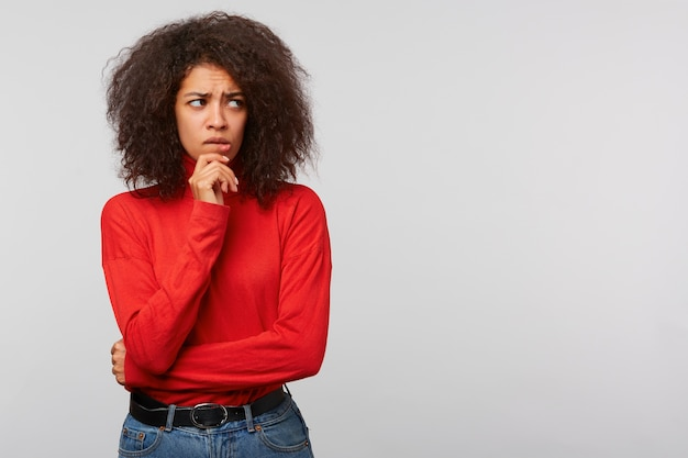 Nervous worried young woman with afro hairstyle, looks aside at blank copy space with thoughtful expression, keeps fist near chin