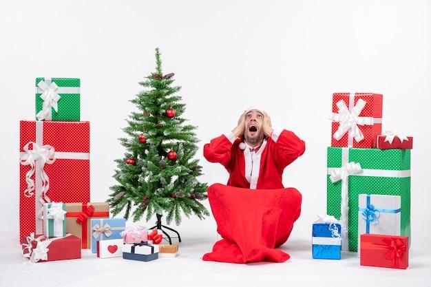 贈り物と装飾されたクリスマスツリーでサンタクロースに扮した神経質な若い大人は、白い背景の上に上を見て地面に座っています