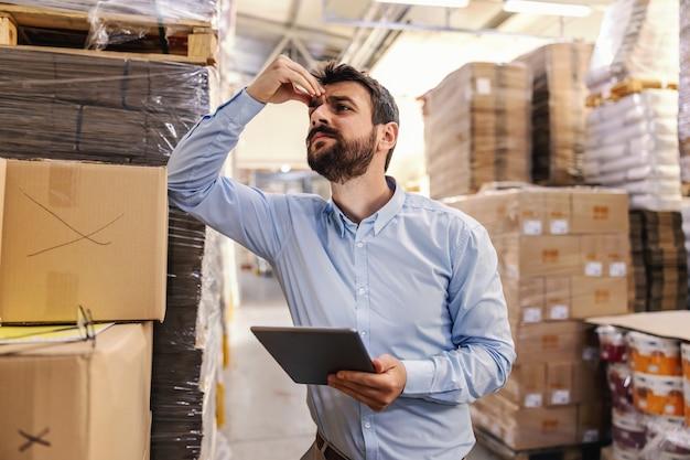 倉庫の箱に寄りかかって、タブレットを持って、頭を抱えながら問題を考えている神経質な若い魅力的なひげを生やしたビジネスマン。