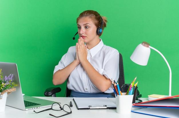 Nervosa ragazza bionda del call center che indossa l'auricolare seduto alla scrivania con strumenti di lavoro che tiene le mani insieme guardando il laptop isolato sul muro verde