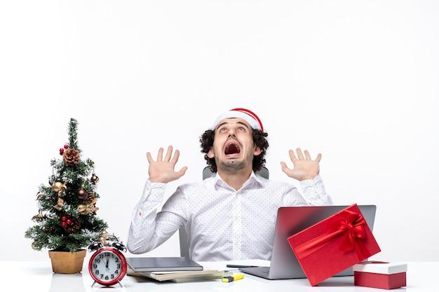 Нервный молодой бизнесмен с забавной шляпой санта-клауса празднует рождество в офисе на белом фоне