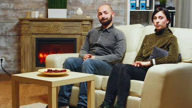 Nervous young couple sitting on couch at couple therapy.