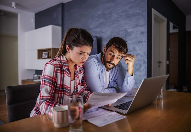 Nervous young couple sitting at home, paying bills online.