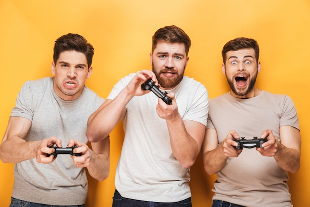 Nervous young group of men friends play games with joysticks.