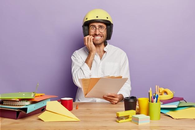 Nervoso giovane designer maschio tiene documenti cartacei, morde le unghie, indossa un casco protettivo e una camicia bianca, si siede al desktop con cose diverse