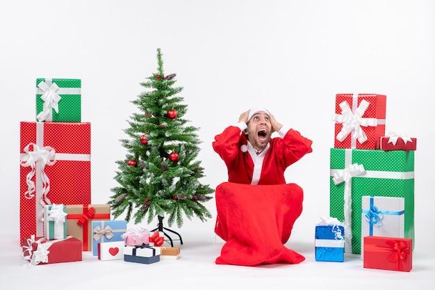 贈り物と白い背景の上の地面に座って飾られたクリスマスツリーでサンタクロースに扮した神経質な若い男