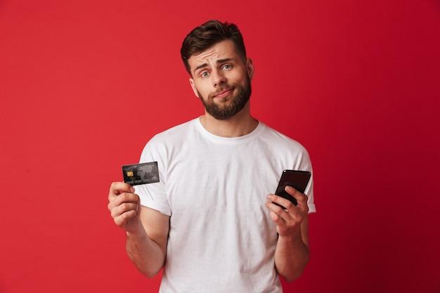 Нервный молодой человек, держащий мобильный телефон и кредитную карту. смотрю камеру.