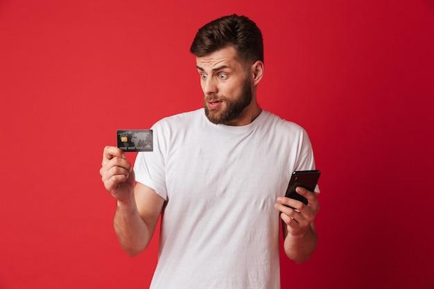 携帯電話とクレジットカードを保持している緊張の若い男。